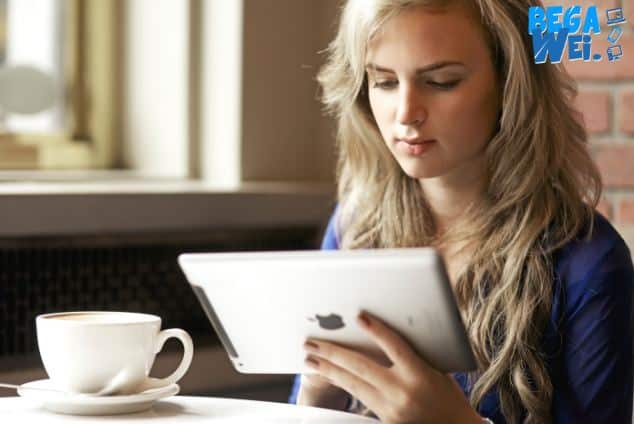 Beautiful young woman reading from her ipad while enjoying her cappuccino at a coffee shop